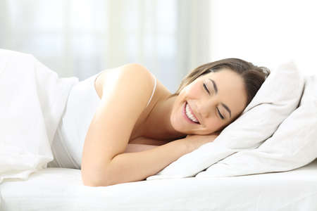 Happy woman with closed eyes sleeping comfortable in a bed at home