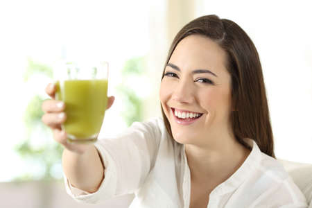 Satisfied woman showing a glass of vegetable juice sitting on a couch in the living room at home