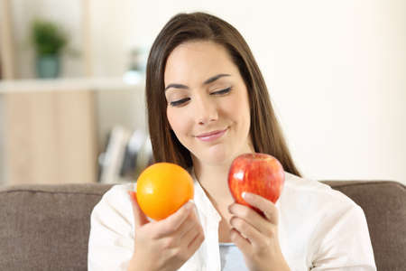 Girl deciding between two fruits an apple and an orange sitting on a couch in the living room at home
