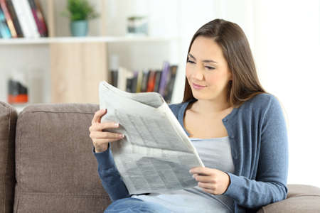 Serious woman reading a newspaper sitting on a couch in the living room at home
