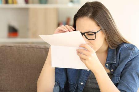 femme ayant des problèmes de la vue à lire une lettre assis sur un canapé dans le salon à la maison