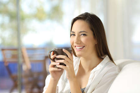 Woman looking at camera holding a coffee mug sitting on a couch in the living room at home Stock Photo