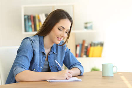 Relaxed girl writing in a notebook on a table at home