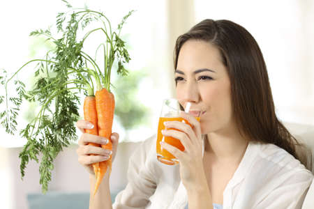 Woman drinking carrot juice sitting on a couch in the living room at home