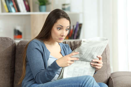 Upset woman reading surprising news in a newspaper sitting on a couch in the living room at home
