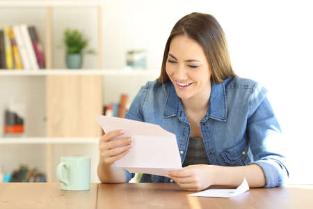 Happy woman reading a letter on a table at home Imagens