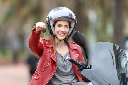 Satisfied biker showing motorbike keys on her scooter on the street