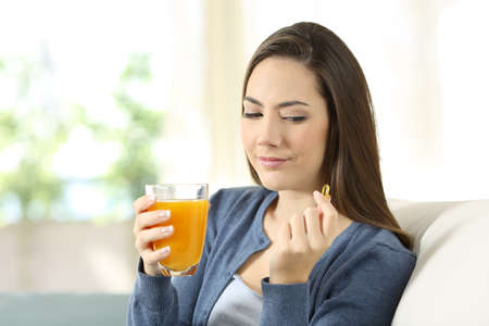 Woman doubting between vitamin pill or orange juice sitting on a couch in the living room at home