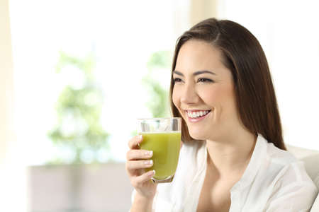 Woman drinking a vegetable juice looking away sitting on a couch in the living room at home