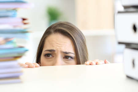 Close up of a scared businesswoman face looking at paperwork on a desktop at office Stock Photo