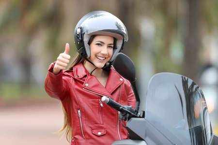 Happy biker looking at you with thumb up on her motorbike outdoors on the street