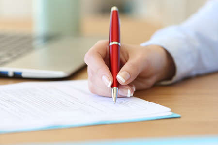 Close up of a businesswoman hand signing a contract on a desk at office Stock Photo