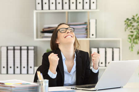 Excited businesswoman celebrating success looking above at office Stock Photo