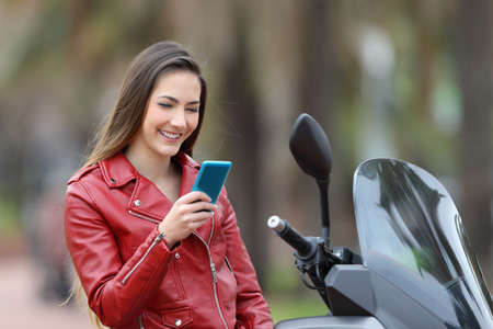Happy biker checking smart phone on her motorbike on the street