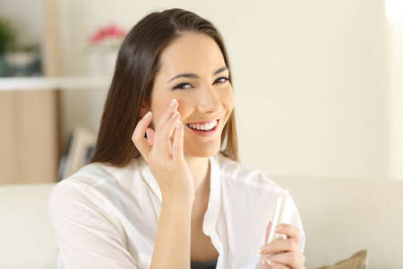 Woman applying moisturizer cream on the face and looking at camera sitting on a couch in the living room at home 写真素材