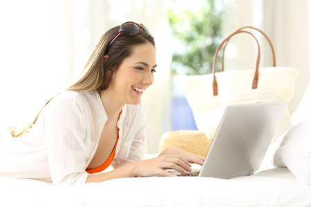 Happy woman using a laptop lying on a bed in a room on summer vacations