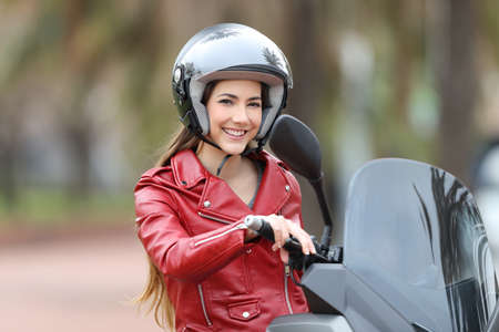 Happy biker wearing an helmet sitting on her motorbike looking at camera on the street 스톡 콘텐츠