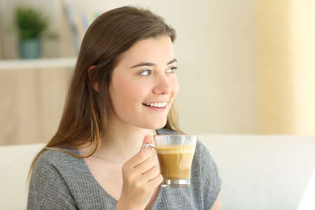 Portrait of a happy teen drinking coffee with milk looking at side with a warm light at home