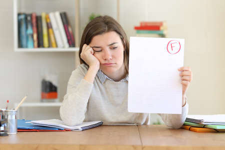 Sad student showing a failed exam to camera at home Stok Fotoğraf - 99049401
