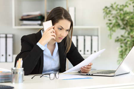 Angry executive calling on phone reading a paper document at office Stock Photo