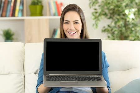 Front view portrait of a single happy woman showing a blank laptop screen sitting on a couch in the living room at home