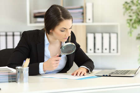 Suspicious executive analyzing meticulously a document at office Stock Photo