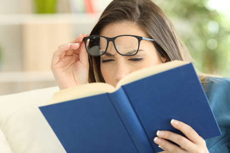 Woman suffering eyestrain trying to read a book at home Stockfoto