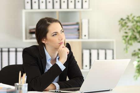 Zamyślony pracownik biurowy zastanawiający się, patrząc na bok siedząc na biurku w miejscu pracy