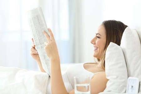 Side view portrait of a happy woman reading a newspaper lying on the bed at home in the morning