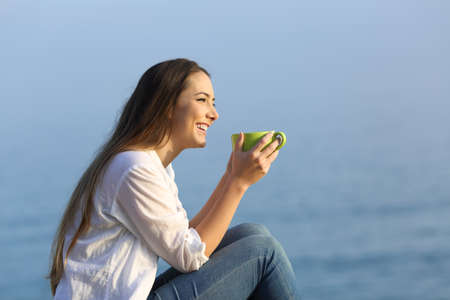 Side view portrait of a happy girl drinking coffee looking away on the beach at sunset 版權商用圖片