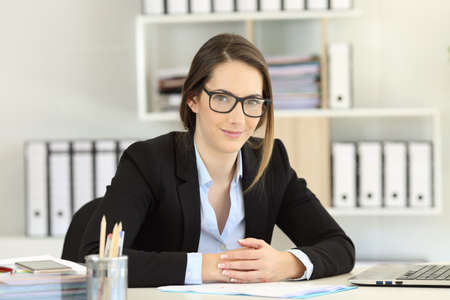 Fronf view portrait of a proud office worker wearing eyeglasses looking at camera Stock Photo