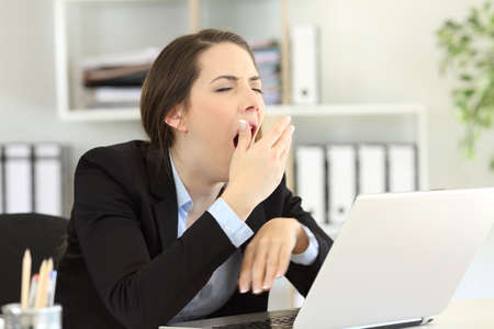 Esecutivo stanco che sbadiglia e che copre la bocca con la mano in ufficio