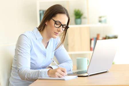 Gravi lavoratori autonomi prendendo appunti su un notebook su un tavolo a casa