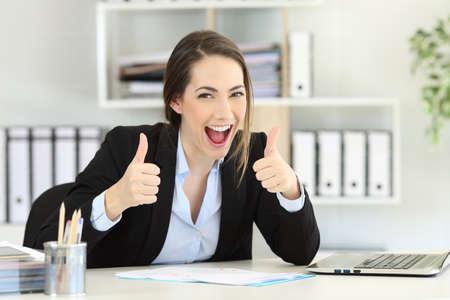 Front view portrait of an excited executive looking at camera with thumbs up at office