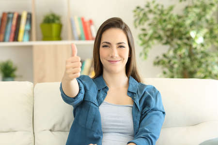 Satisfied woman looking at camera with thumbs up sitting on a couch in the living room at home Фото со стока