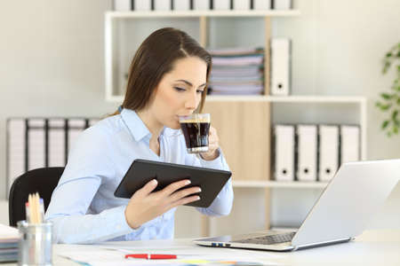 Office worker working online with multiple devices and drinking coffee Stock Photo