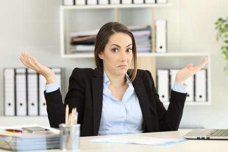 Vooraanzicht portret van een verwarde zakenvrouw schouderophalend schouders kijken camera op kantoor