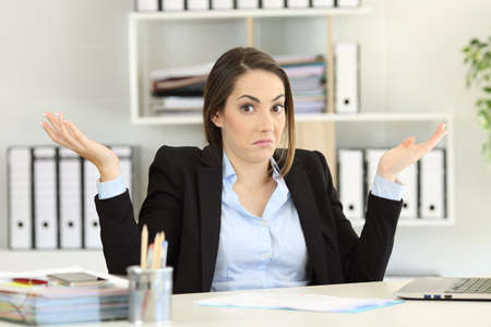 Vorderansicht Porträt einer verwirrten Geschäftsfrau , die Schultern zuckt , die Kamera im Büro betrachtet