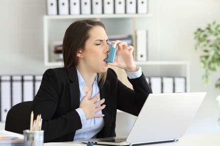 Ejecutivo de asma que tiene un ataque de asma inhalando con un inhalador en la oficina