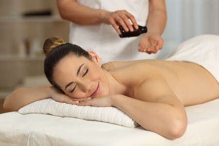 Massage therapist applying oil in hands ready to begin in a spa salon