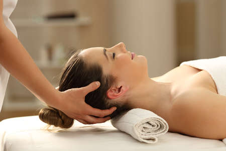 Side view portrait of a woman receiving a head massage in a spa Stock Photo