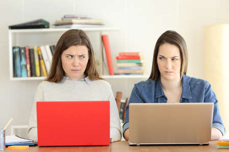 Front view portrait of two angry students studying looking each other with hate