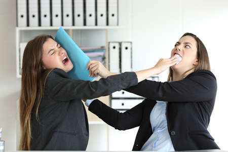Two angry executives fighting hitting with folders at office
