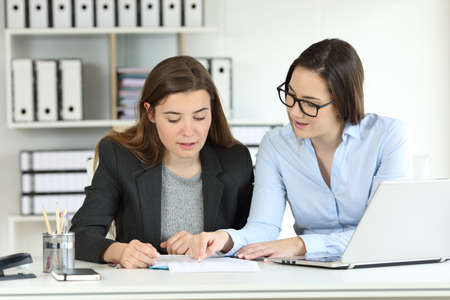 Twee geconcentreerde kantoormedewerkers die samen praten over documenten op een desktop