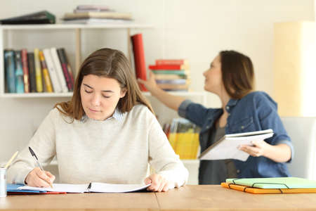 Front view portrait of two college students studying at home Stock Photo