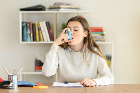 Student having an asthma attack using an asthma inhaler at home Archivio Fotografico - 100045267