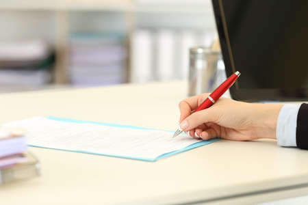 Close up portrait of an executive hand signing a form or contract on a desktop at office