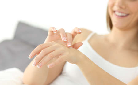 Close op of a happy woman hands applying moisturizer cream Фото со стока