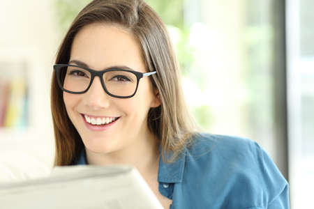 Happy woman holding a newspaper wearing eyeglasses looking at you at home