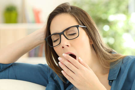 Fatigued woman yawning covering the mouth with a hand at home